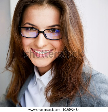 Beautiful young business woman wearing glasses sitting relaxed at her office and looking at camera - stock photo