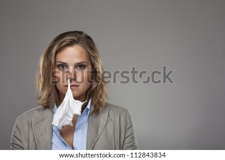 Beautiful young business woman with a tissue hanging from nose - stock photo