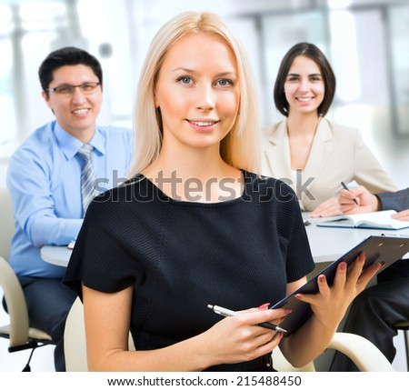 Beautiful young business woman with colleagues on the background - stock photo