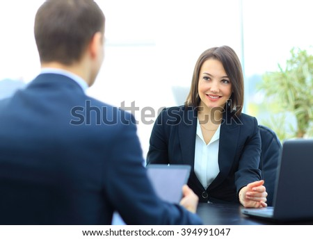 Beautiful young businesswoman conducting a job interview seated at her desk