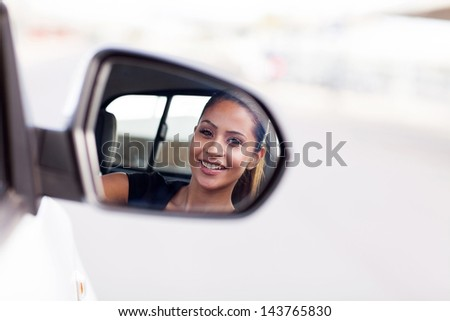 beautiful young businesswoman driver looking at side mirror