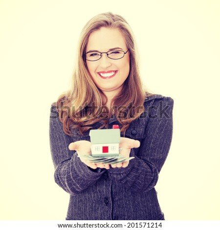 Beautiful young businesswoman holding euros bills and house model ,real estate loan concept - stock photo