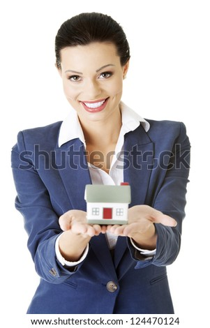 Beautiful young businesswoman holding house model over white - real estate loan concept - stock photo