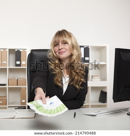 Beautiful young businesswoman holding out a fistful of banknotes as she stretches across her desk conceptual of success, a bribe or pay-off - stock photo