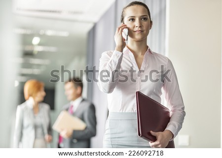 Beautiful young businesswoman on call with colleagues in background at office corridor - stock photo