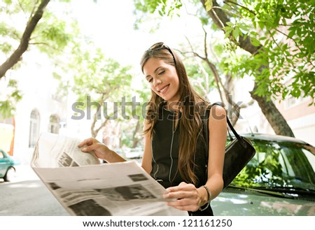 Beautiful young businesswoman reading a newspaper while leaning on a car in the financial district of a classic city street aligned with trees on a sunny day. - stock photo