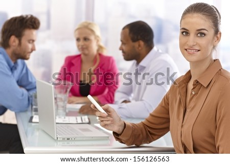 Beautiful young businesswoman sitting at a meeting, using cellphone.