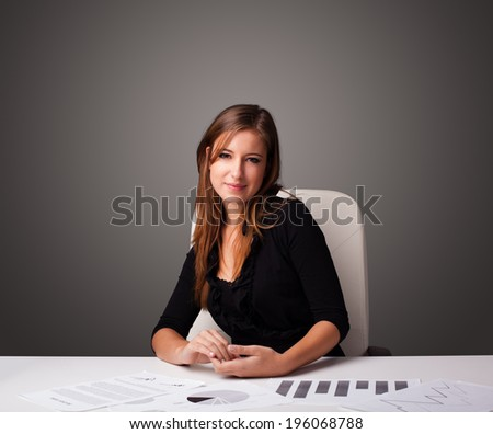 Beautiful young businesswoman sitting at desk and doing paperwork - stock photo