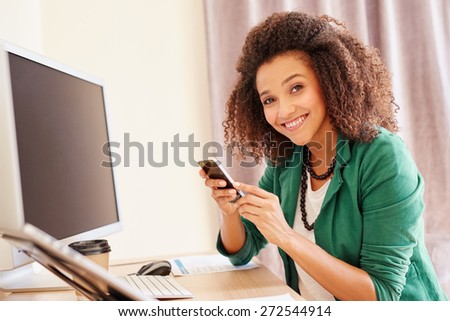 Beautiful young businesswoman sitting at her desk while making a call on her mobile phone