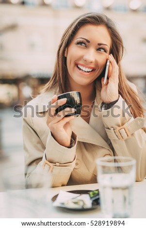 Beautiful young businesswoman sitting in a street cafe, having her cup of coffee and using smart phone.