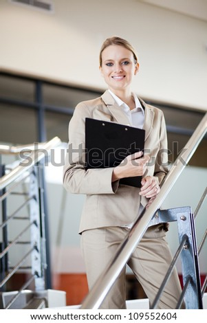 beautiful young businesswoman standing by stairs - stock photo