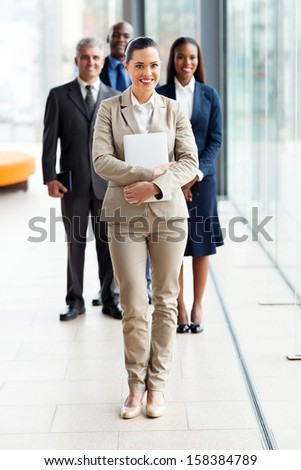 beautiful young businesswoman standing in front of colleagues