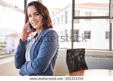Beautiful young businesswoman standing in her office and smiling at the camera while using her mobile phone - stock photo