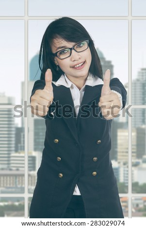 Beautiful young businesswoman standing near the window and showing thumbs up - stock photo