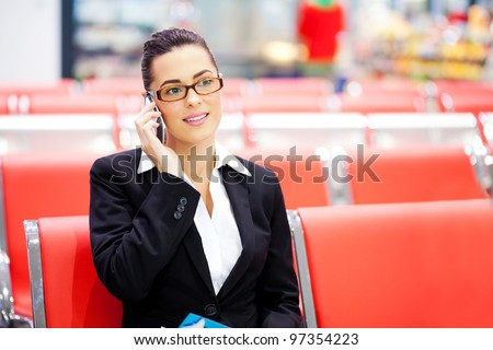 beautiful young businesswoman talking on cell phone at airport