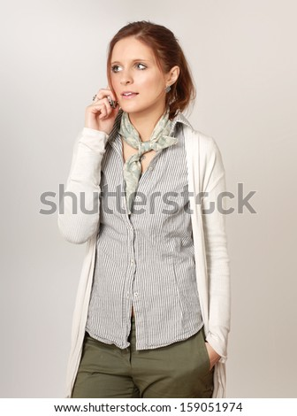 Beautiful young businesswoman talking on cellphone, isolated on grey - stock photo