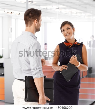 Beautiful young businesswoman talking to businessman, smiling. - stock photo