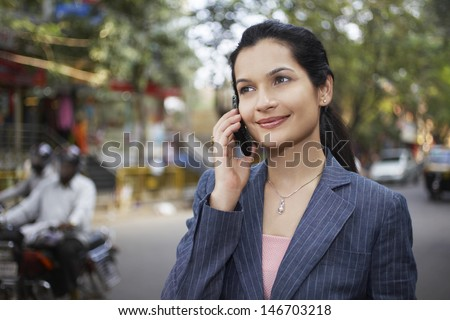 Beautiful young businesswoman using cell phone on city street - stock photo
