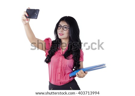 Beautiful young businesswoman using smartphone to take selfie photo in the studio, isolated on white background - stock photo