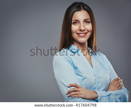 Beautiful young businesswoman with arms crossed looking confident against a gray background - stock photo