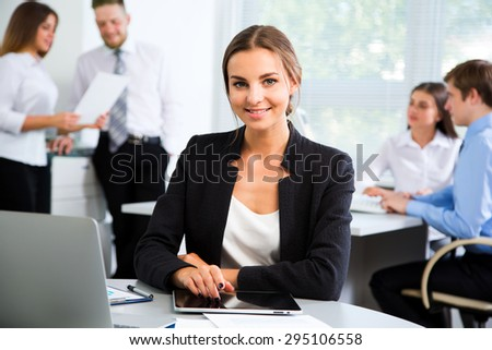 Beautiful young businesswoman with colleagues discussing in the background - stock photo
