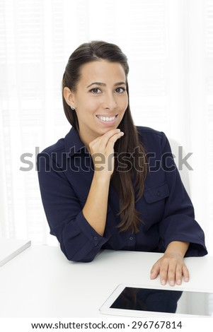 Beautiful young businesswoman with had on her chin sitting at the desk in the office and looking at camera. - stock photo