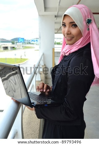 Beautiful young businesswomen smile with laptop.