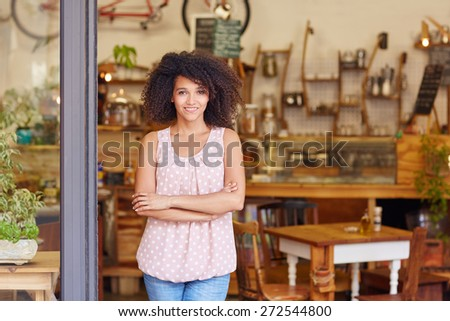 Beautiful young cafe owner proud of her small business standing smiling in the doorway of her coffee shop - stock photo
