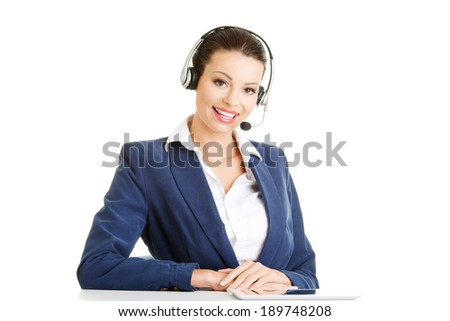 Beautiful young call-center assistant at the desk, isolated on white - stock photo