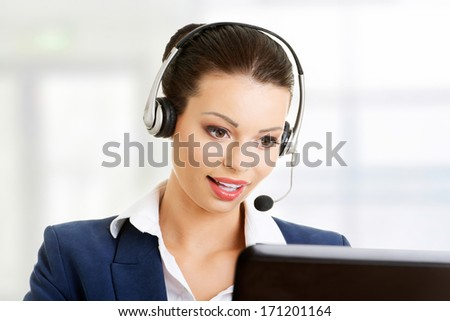 Beautiful young call-center assistant smiling  - stock photo