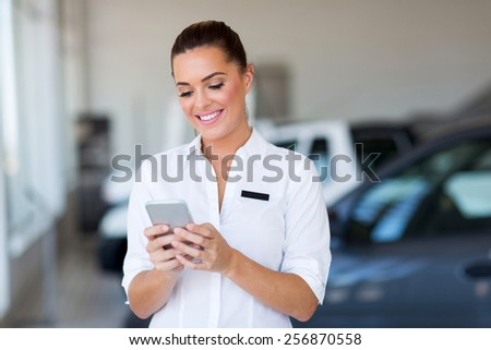 beautiful young car sales consultant using smart phone at showroom - stock photo