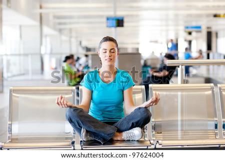 beautiful young casual woman doing yoga meditation at airport - stock photo