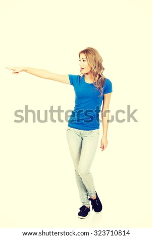 Beautiful young casual woman pointing aside. - stock photo