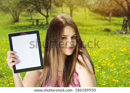 Beautiful young Caucasian brunette woman in park on sunny summer day showing tablet computer with blank screen smiling looking at camera.