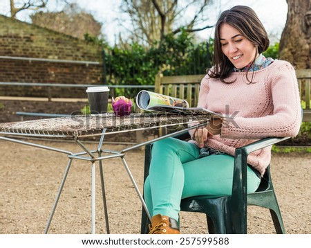 Beautiful Young Caucasian Girl Drinking Coffee in a Cafe and Reading a Magazine - stock photo