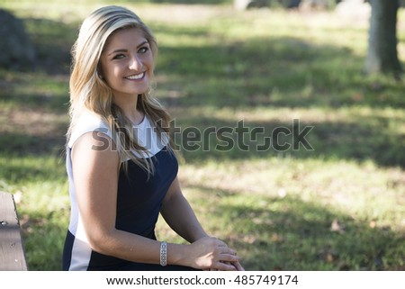 Beautiful young Caucasian woman in business attire (black and white dress) stands in a park