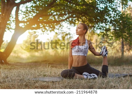Beautiful young caucasian woman in fitness wear doing exercises in a park - stock photo