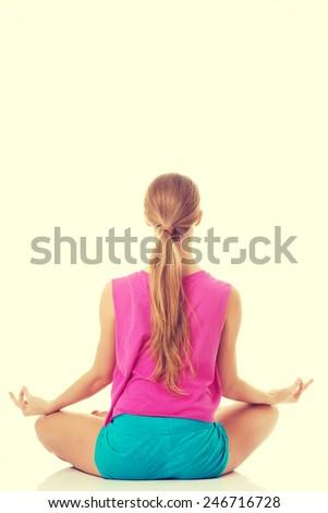 Beautiful young caucasian woman is exercising, doing yoga.  - stock photo