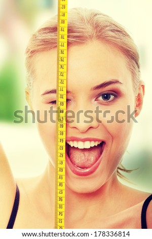 Beautiful young caucasian woman measuring her body with tape, isolated on white background