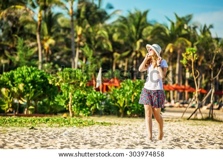 Beautiful young caucasian woman on the beach in white hat talking on mobile phone and laughing. Palm trees on background - stock photo