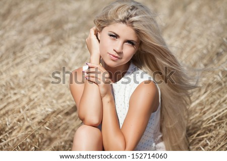 beautiful young Caucasian woman outdoor, healthy sensual girl at wheat field. Happy  blonde woman resting. Natural makeup hairstyle. long hair perfect skin. young woman outdoors. Natural blond hair - stock photo