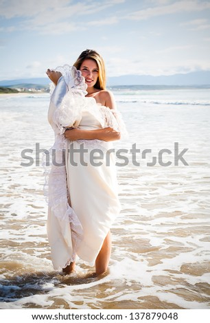 beautiful young caucasian woman playing in the sea wearing an ivory evening gown