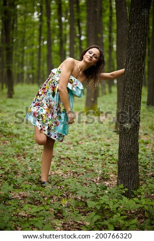 Beautiful young caucasian woman posing outdoor in the woods - stock photo
