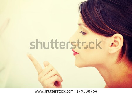 Beautiful young caucasian woman putting a contact lens at bathroom - stock photo
