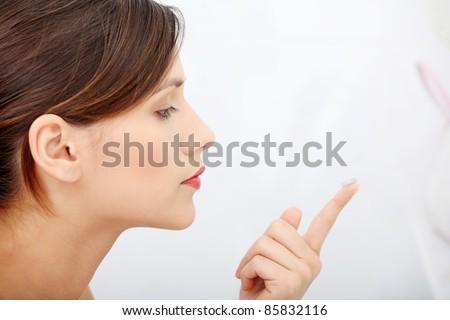 Beautiful young caucasian woman putting a contact lens at bathroom - stock photo