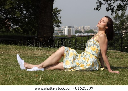 Beautiful young caucasian woman sitting on grass in city park, head upturned with eyes closed enjoying the sunshine. She is wearing yellow summer dress and white deck shoes. - stock photo