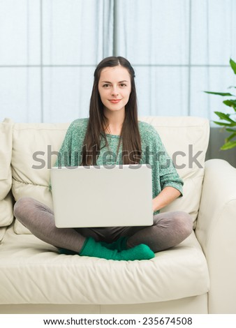 beautiful young caucasian woman sitting on sofa at home holding laptop on her legs - stock photo