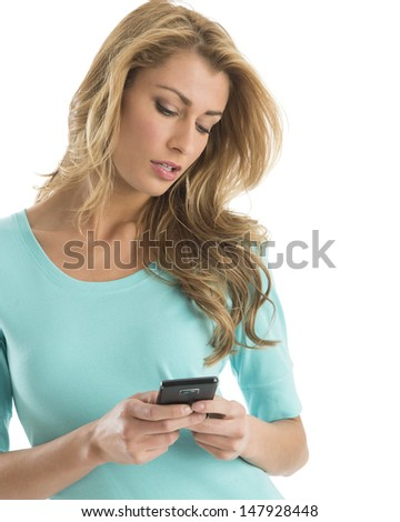Beautiful young Caucasian woman text messaging through smart phone against white background