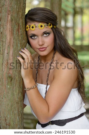 Beautiful young Caucasian woman wearing a white dress and floral headband sits on a tree branch in a park - 1960's fashion headshot - stock photo