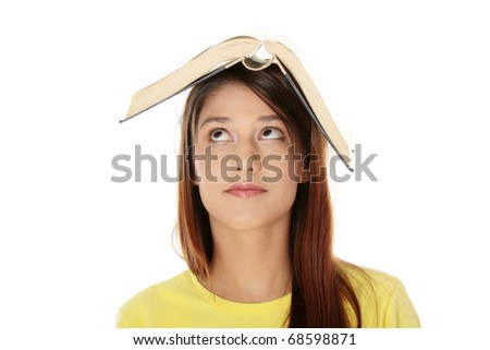 Beautiful young caucasian woman with book on her head,looking up
